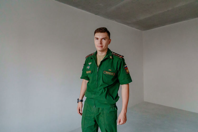 Portrait of soldier standing against wall