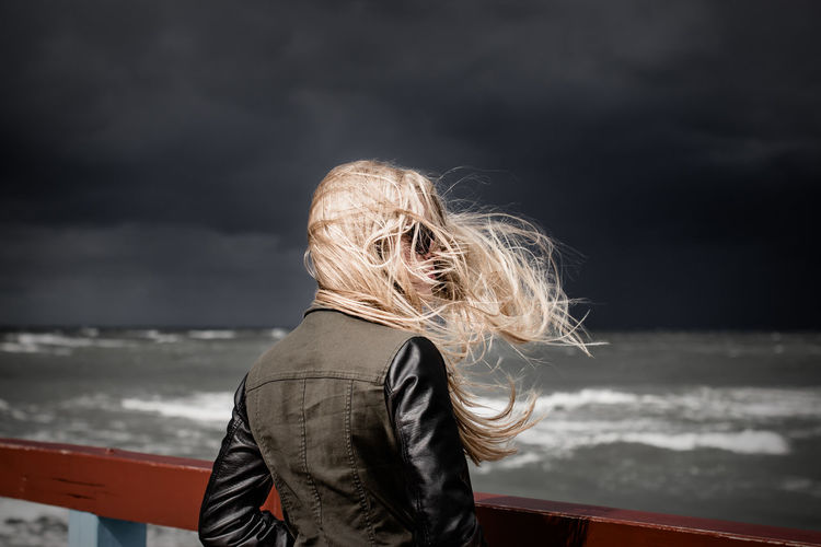 Woman with tousled hair standing by railing at beach against storm clouds