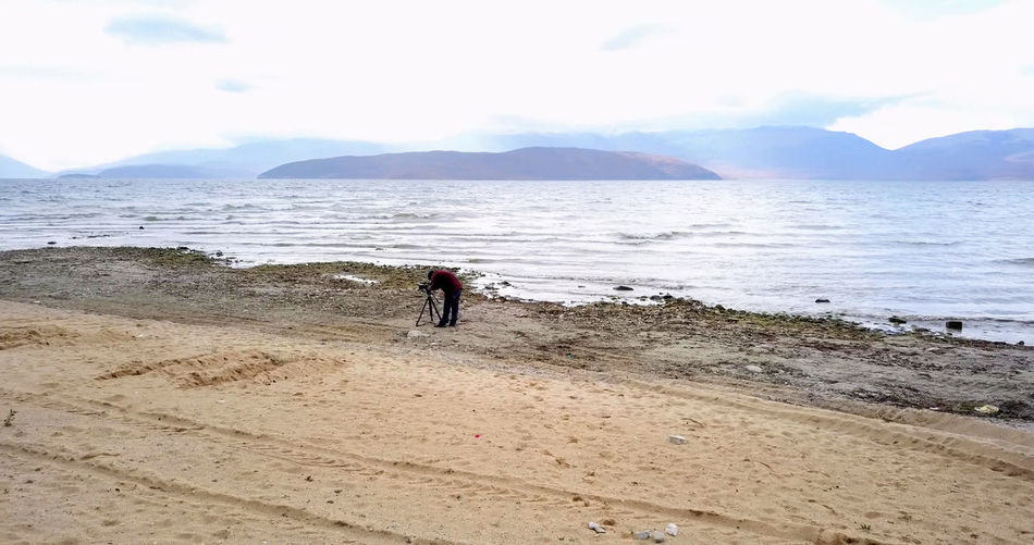 Man with tripod standing against sea at beach