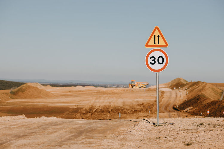 Road sign in desert against clear sky