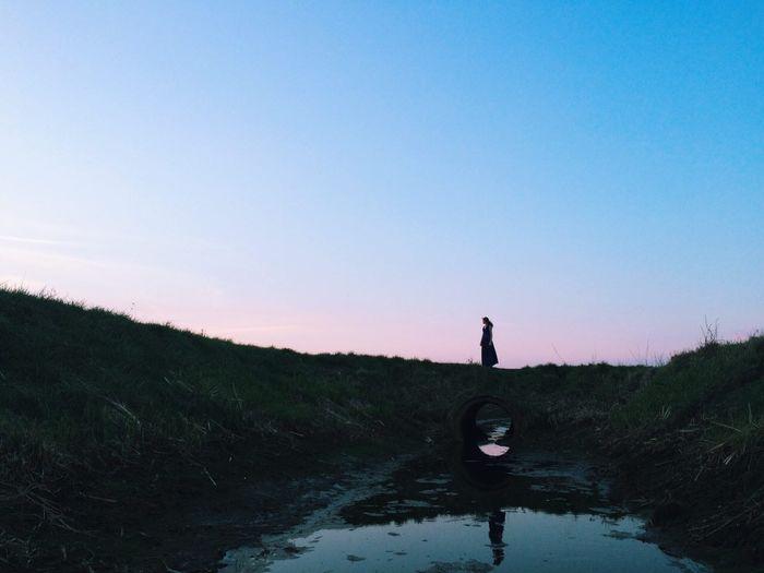 Woman standing by stream on field against clear sky