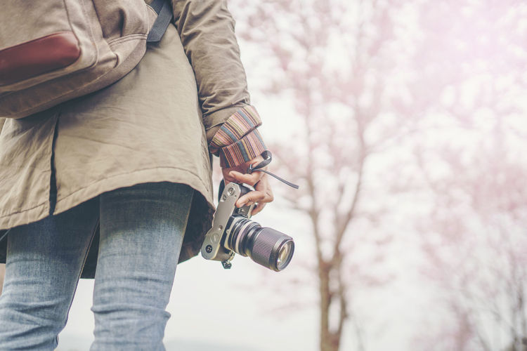 hand holding camera with beautiful natural background Camera Tourist Adventure Backpack Casual Clothing Flower Hand Hipster Holding Jeans Lifestyles Nature One Person Outdoors Photography Plant Real People Standing Tree