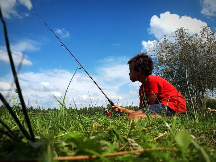 Side View Of Boy With Fishing Rod Sitting On Grassy Field Against Sky
