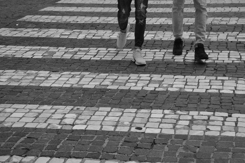 Low section of people walking on cobblestone street