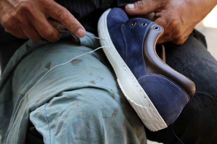 Midsection of man stitching shoe at workshop