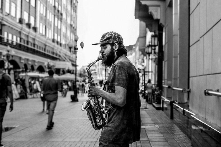 Man playing saxophone in city