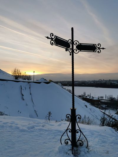 Street light on snow covered field against sky during sunset