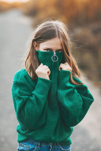 Beautiful teenage girl with blonde hair and blue eyes in a warm green sweater in an autumn park.