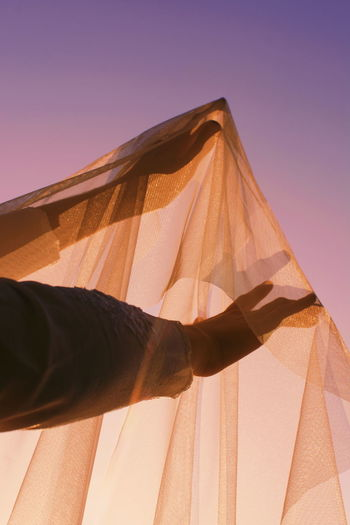 Cropped hand holding fabric against clear sky during sunset