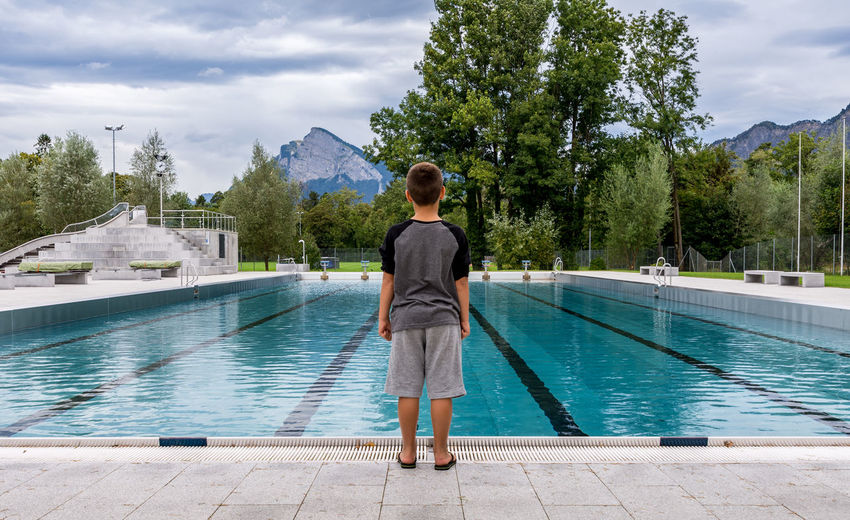 Rear view of boy standing at poolside
