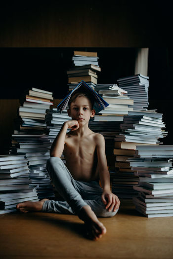 Boy sitting against stack of books