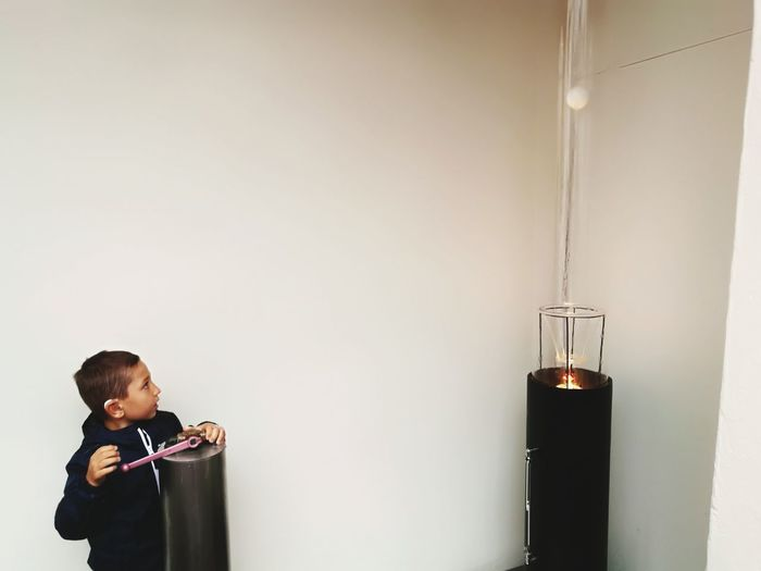 Boy performing scientific experiment against white wall