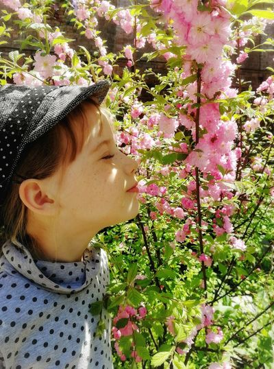 Close-Up Of Girl Smelling Pink Flowers Blooming Outdoors