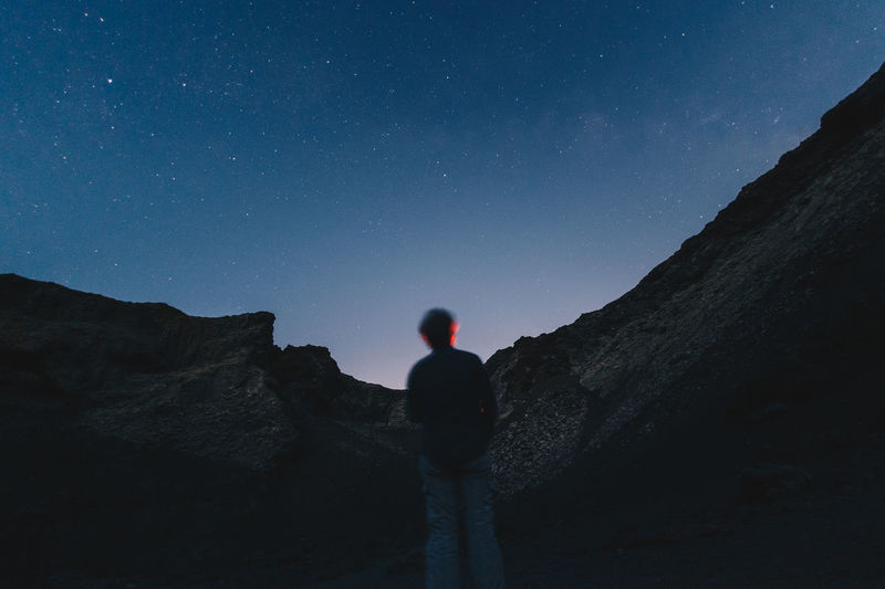 Rear view of man standing on mountain against sky at night