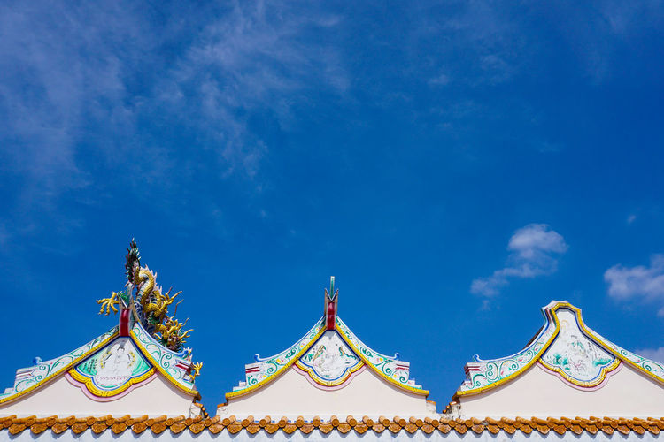 Low angle view of carousel against blue sky