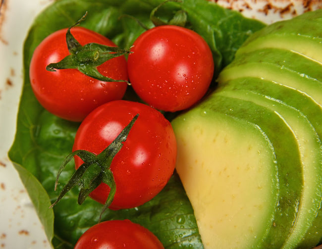 Close up red cherry tomatoes and avocado slices on green salad leaf Vegetable Food And Drink Food Tomato Freshness Healthy Eating Red Green Color Wellbeing Close-up No People Raw Food Full Frame High Angle View Ripe Cherry Tomato Avocado Slices Salad Vegan Vegan Food Vegetarian Food Side Dish