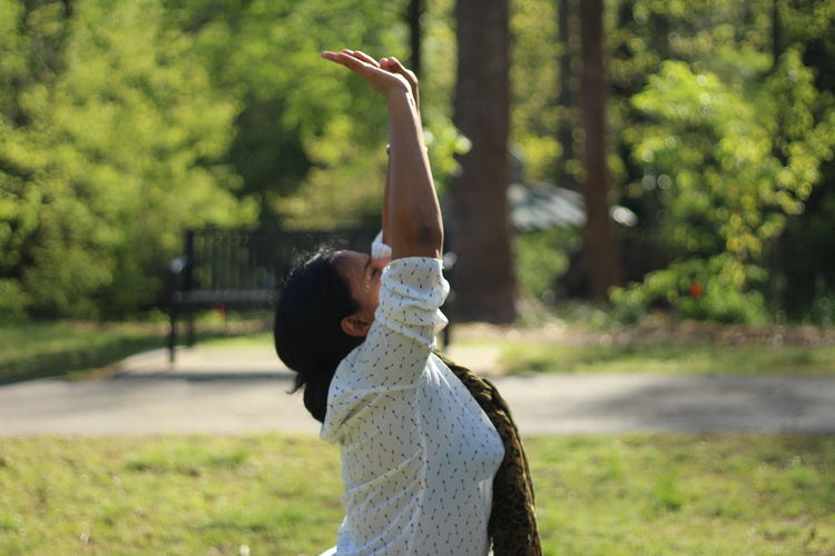 Side View Of Woman With Arms Raised Exercising At Park