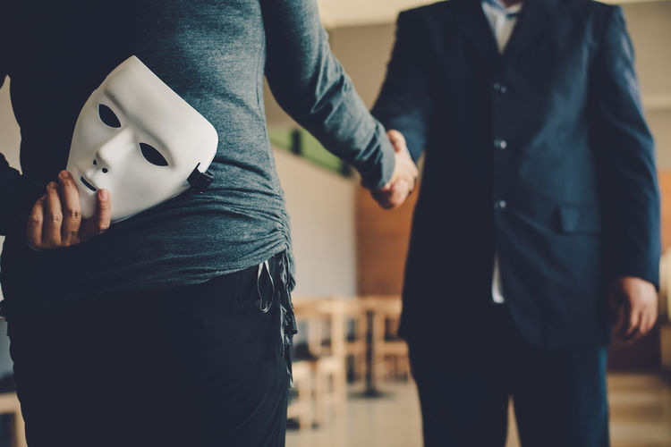 Businesswoman hiding mask while shaking hands with colleague in office