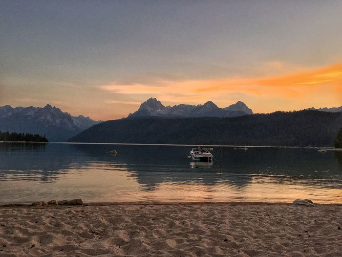 Redfish Lake in Stanley, Idaho Redfish Lake Boat Water Sky Scenics - Nature Sunset Beauty In Nature Mountain Cloud - Sky Tranquil Scene Tranquility No People Lake Reflection Beach Mountain Range Nautical Vessel Nature Outdoors