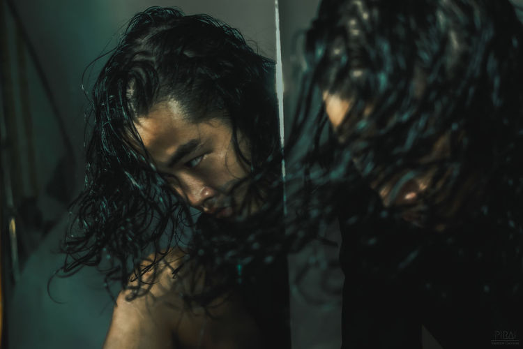 Close-up of man tossing long hair reflecting on mirror