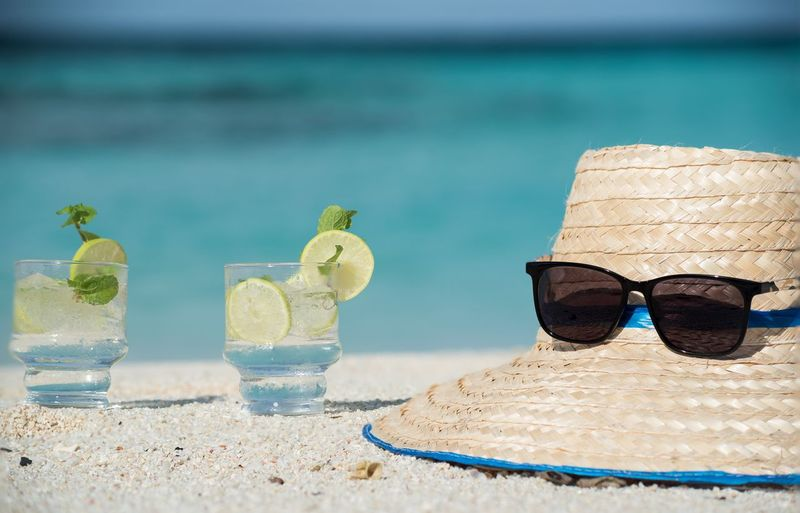 Close-up of drinks by straw hat and sunglasses at beach