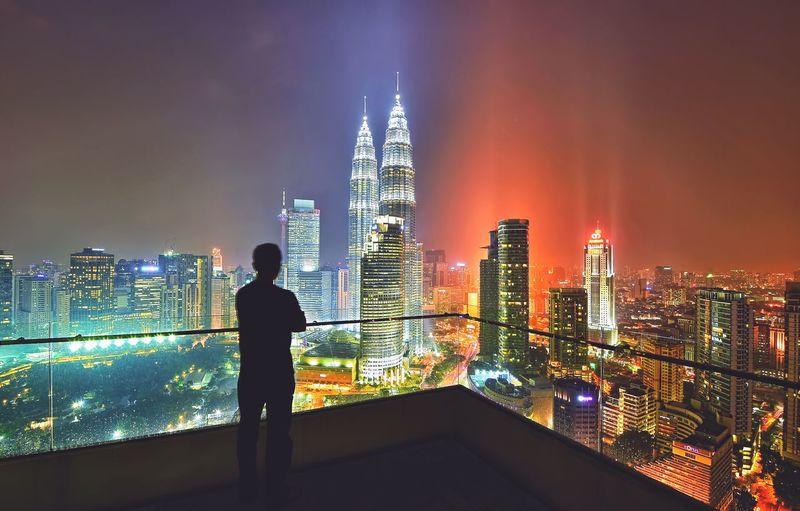 Silhouette man standing over kuala lumpur city at night