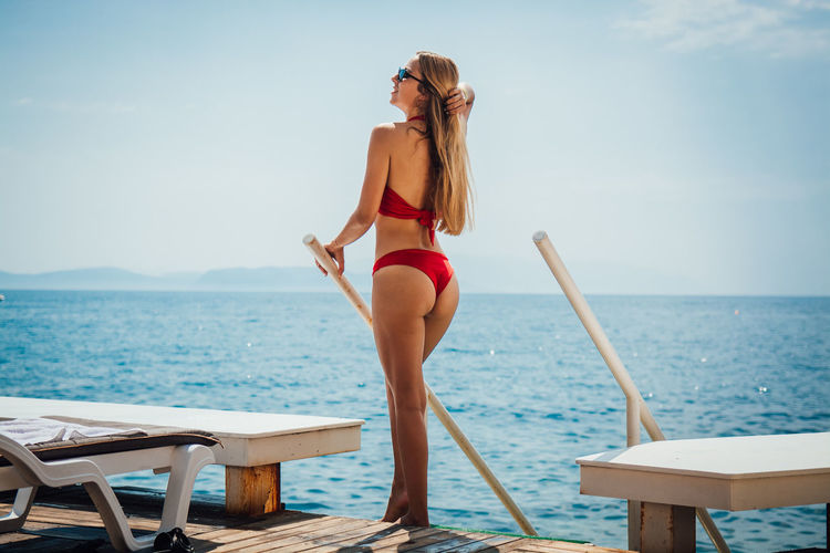 Water Sea One Person Clothing Sky Leisure Activity Young Women Young Adult Swimwear Real People Lifestyles Women Rear View Bikini Hair Standing Adult Horizon Beautiful Woman Horizon Over Water Hairstyle