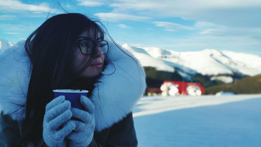 Close-Up Of Woman In Fur Coat Holding Coffee Against Sky During Winter