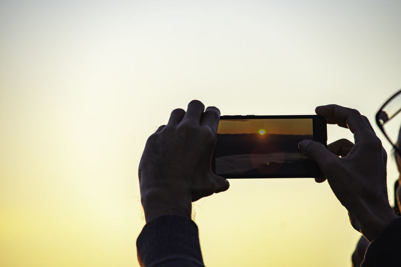 Midsection of man photographing against sky during sunset