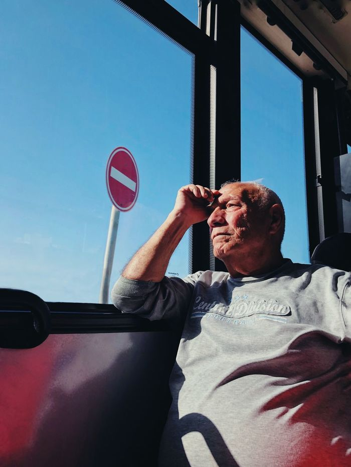 PORTRAIT OF MAN HOLDING MOBILE PHONE WHILE SITTING IN BUS
