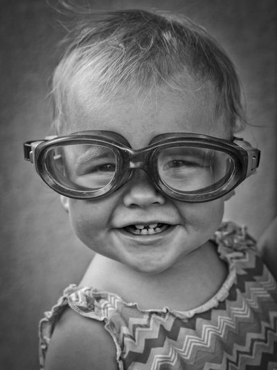 Close-Up Portrait Of Cute Toddler Wearing Eyeglasses