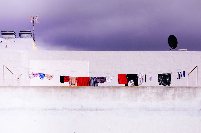 Clothes hanging on snow against sky at dusk