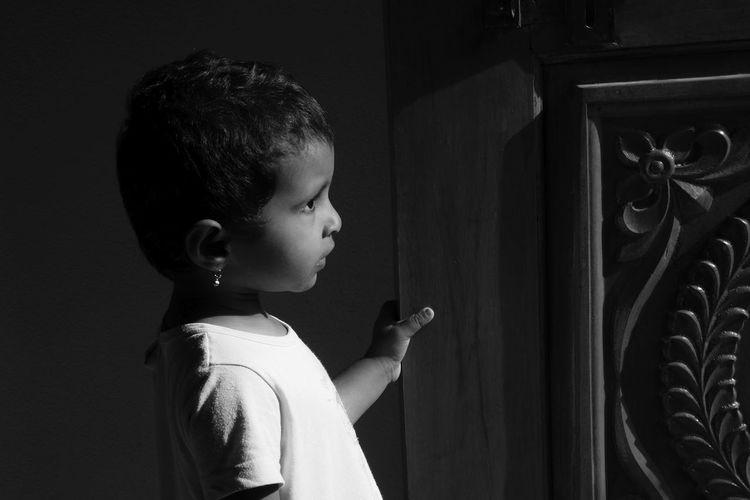 Side view of girl standing at door