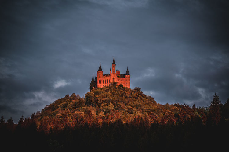 Castle on hill against cloudy sky