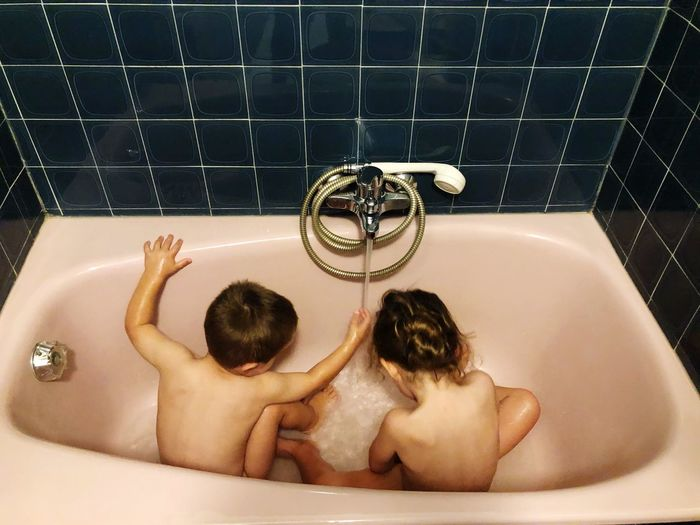 High angle view of naked siblings sitting in bathtub