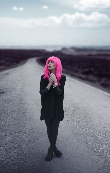 Young woman with dyed hair standing on road against sky