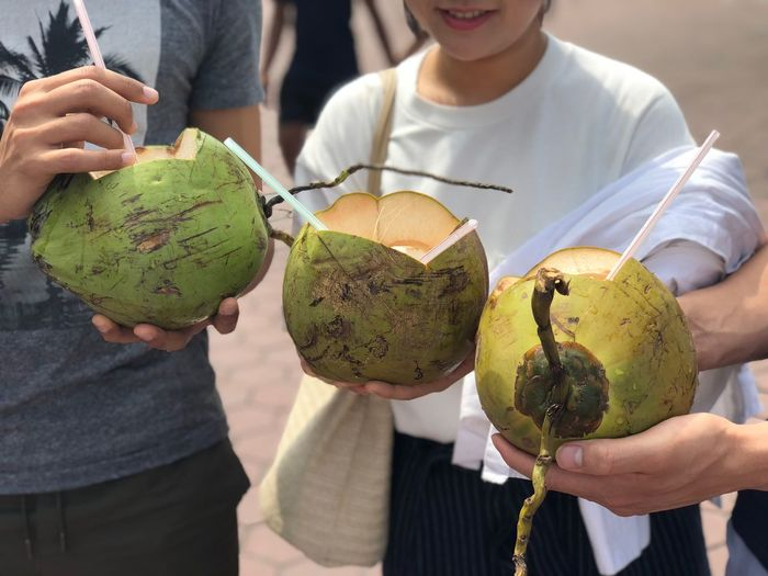Midsection of friends holding coconuts while standing at beach