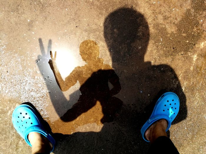 Low section of woman showing peace sign on puddle