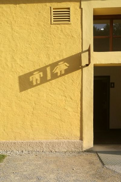 Shadow Building Exterior Architecture Built Structure Door No People Day Salzburg, Austria Shadows & Lights Shadow And Light Shadow Photography Sign Yellow Wall Wall Art Sunlight Signs Men Women Art Another View Another Point Of View Paint The Town Yellow