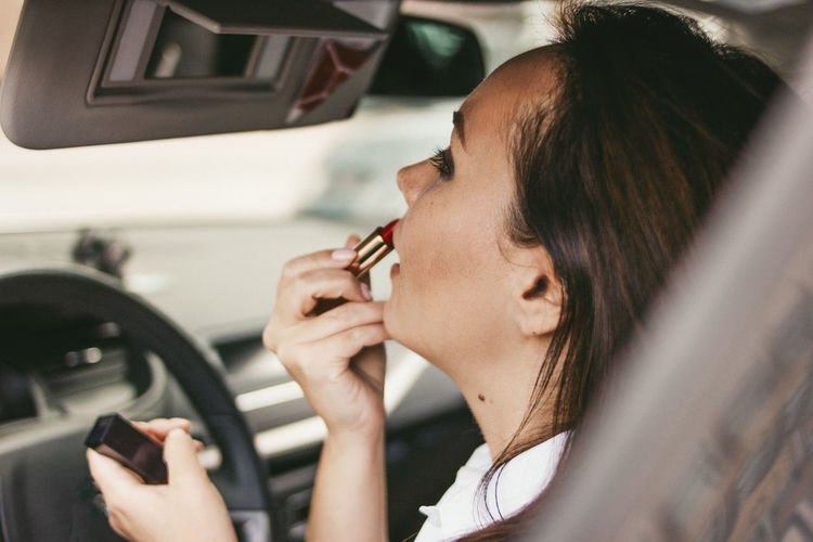 Woman applying lipstick in car