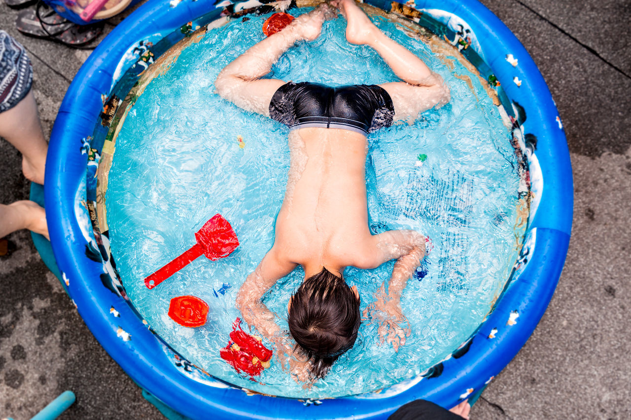 High angle view of shirtless boy playing in children pool