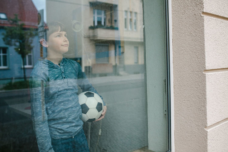 Boy playing with ball in front of window