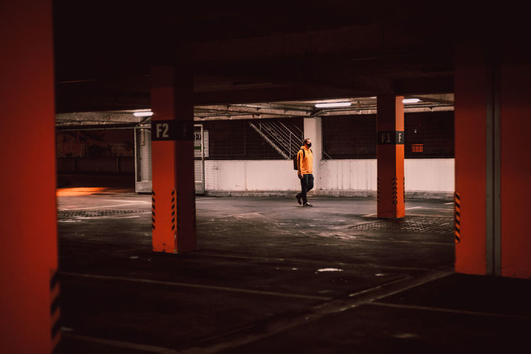 Rear view of man standing by building in garage