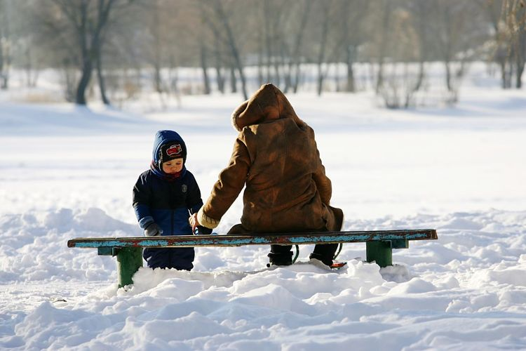Father With Son On Snow Covered Field During Sunny Day
