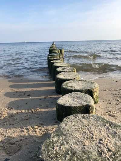 Stones on sea shore against sky