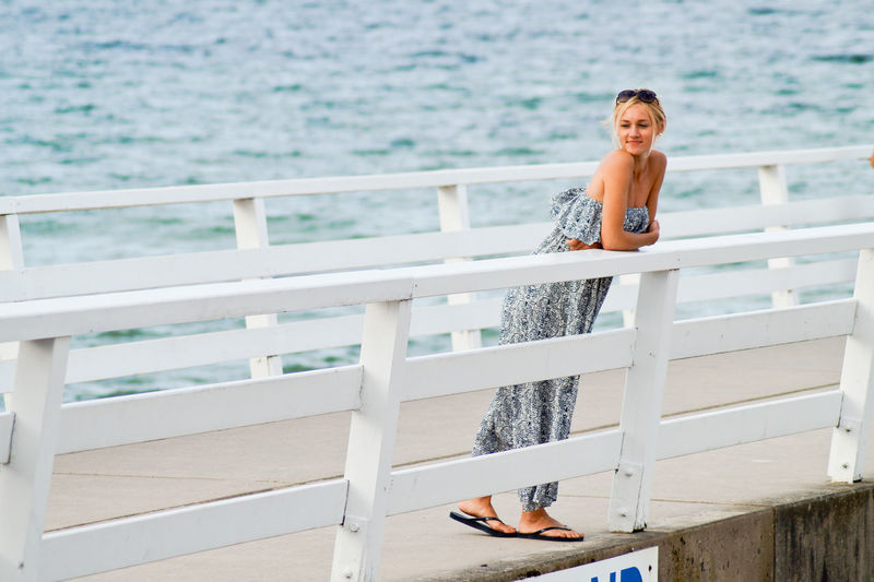 Full length on young woman leaning on railing at pier