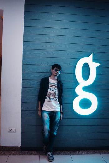 Full length of teenage girl standing against wall