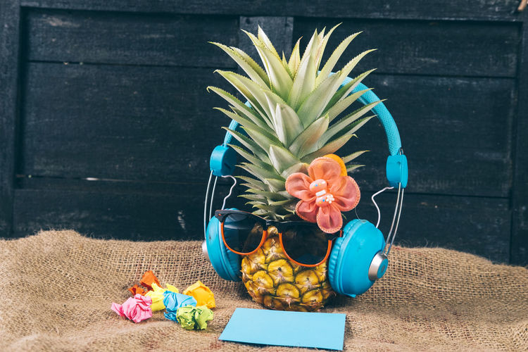 High angle view of sunglasses and headphones over pineapple on table