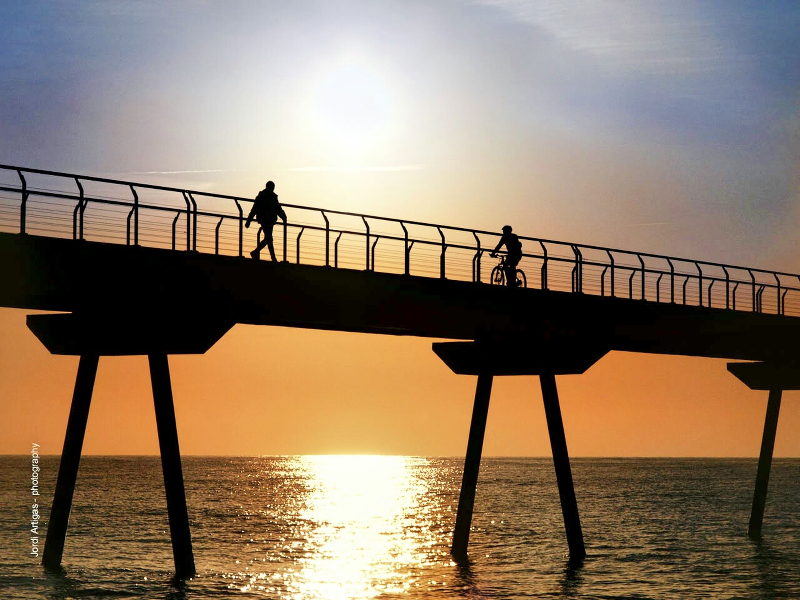 sunset, silhouette, sea, water, sun, horizon over water, sky, orange color, pier, railing, nature, tranquility, scenics, beauty in nature, built structure, low angle view, sunlight, reflection, tranquil scene, outdoors
