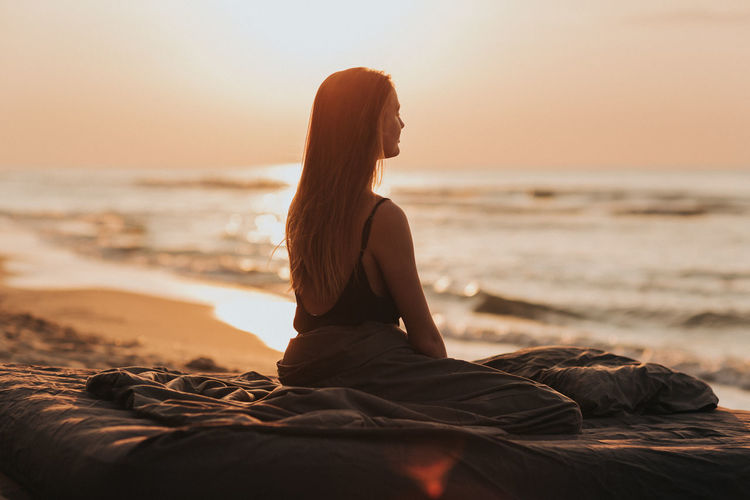 Woman sitting on shore at beach against sky during sunset